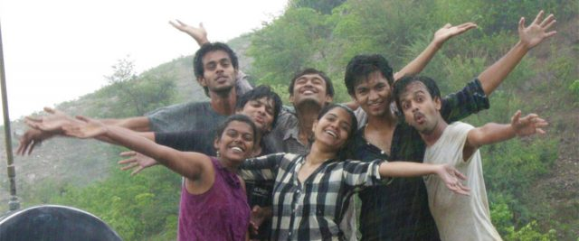 Seven happy people in India standing in the rain.