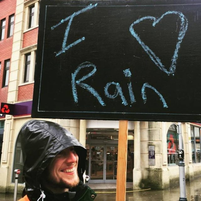 """Stephen Donnelly holding a sign that reads """" I love rain."""""""