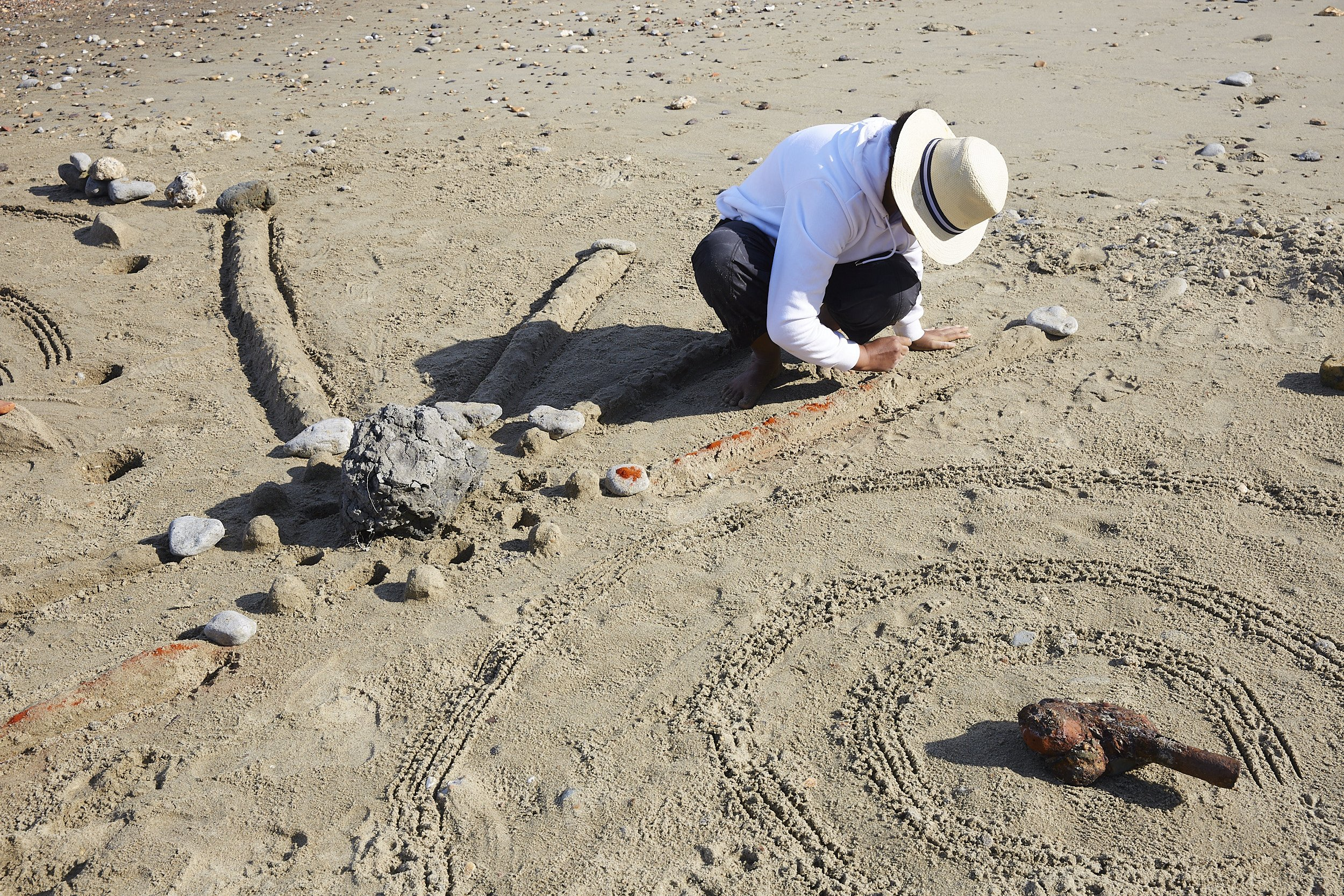 The artist sprinkles red powder along a long mound of sand that ends in a rock on either side.