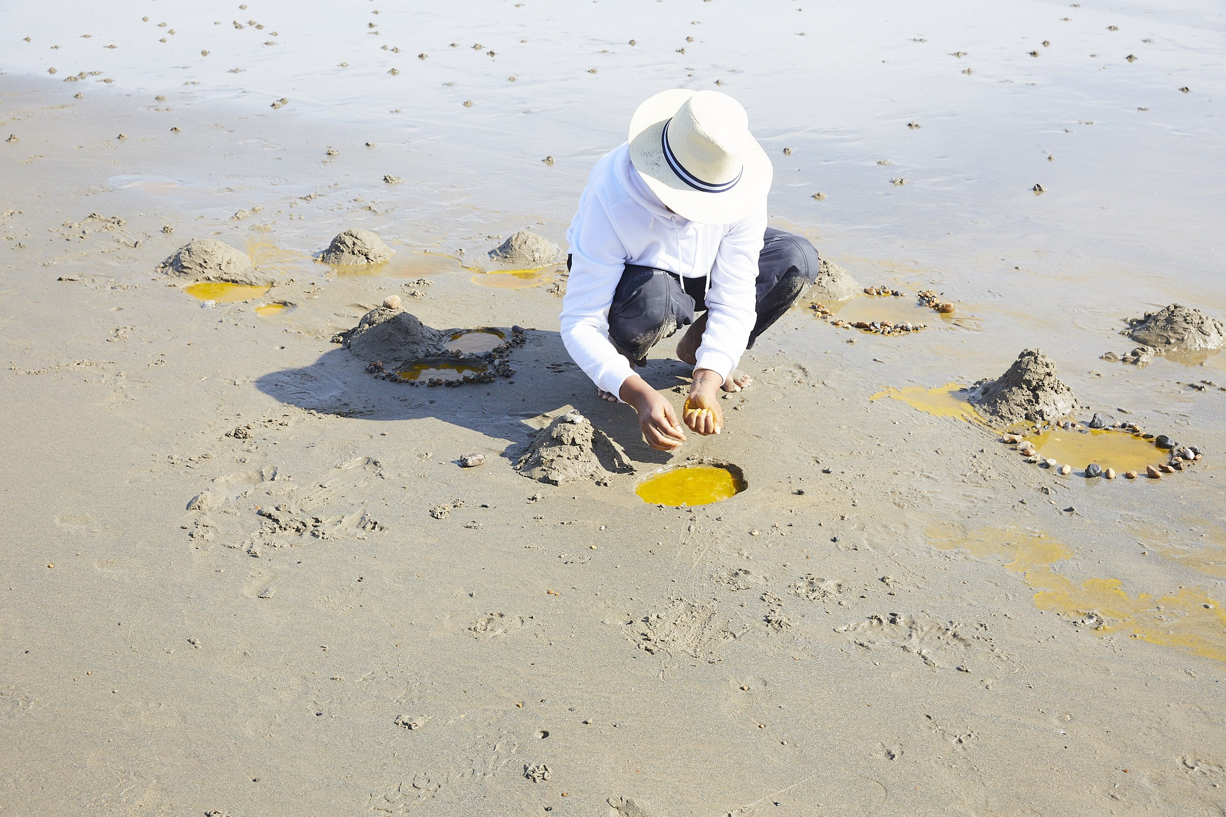 The artist kneeling by a circular tidal pool, adding yellow colouring to the water. Several other yellow pools and mounds of sand dot the shoreline.