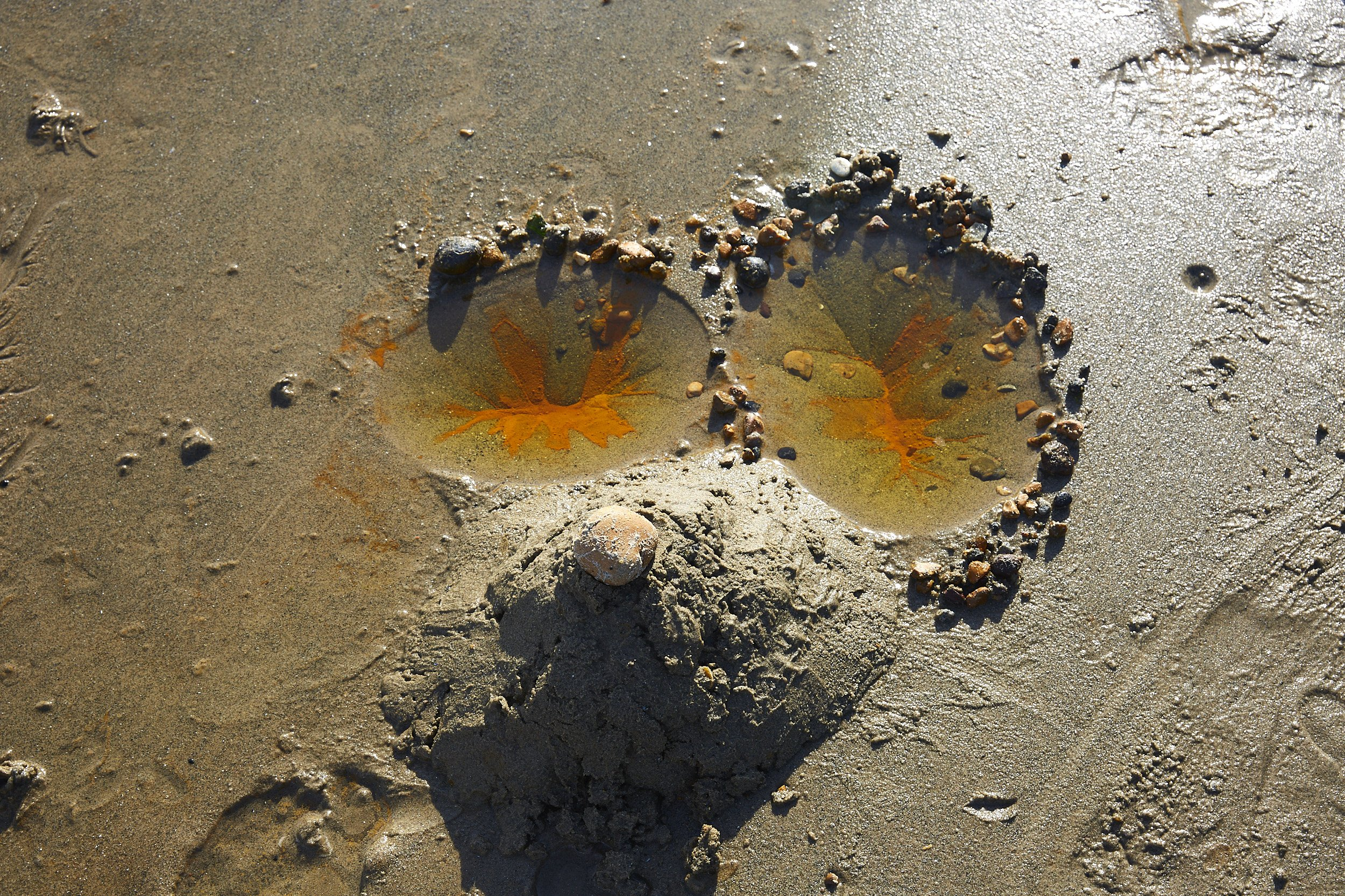 Two circular depressions in wet sand surrounded by pebbles. The centre of each depression has rusty red sand, and below them as a small mound of sand with a rock atop it.