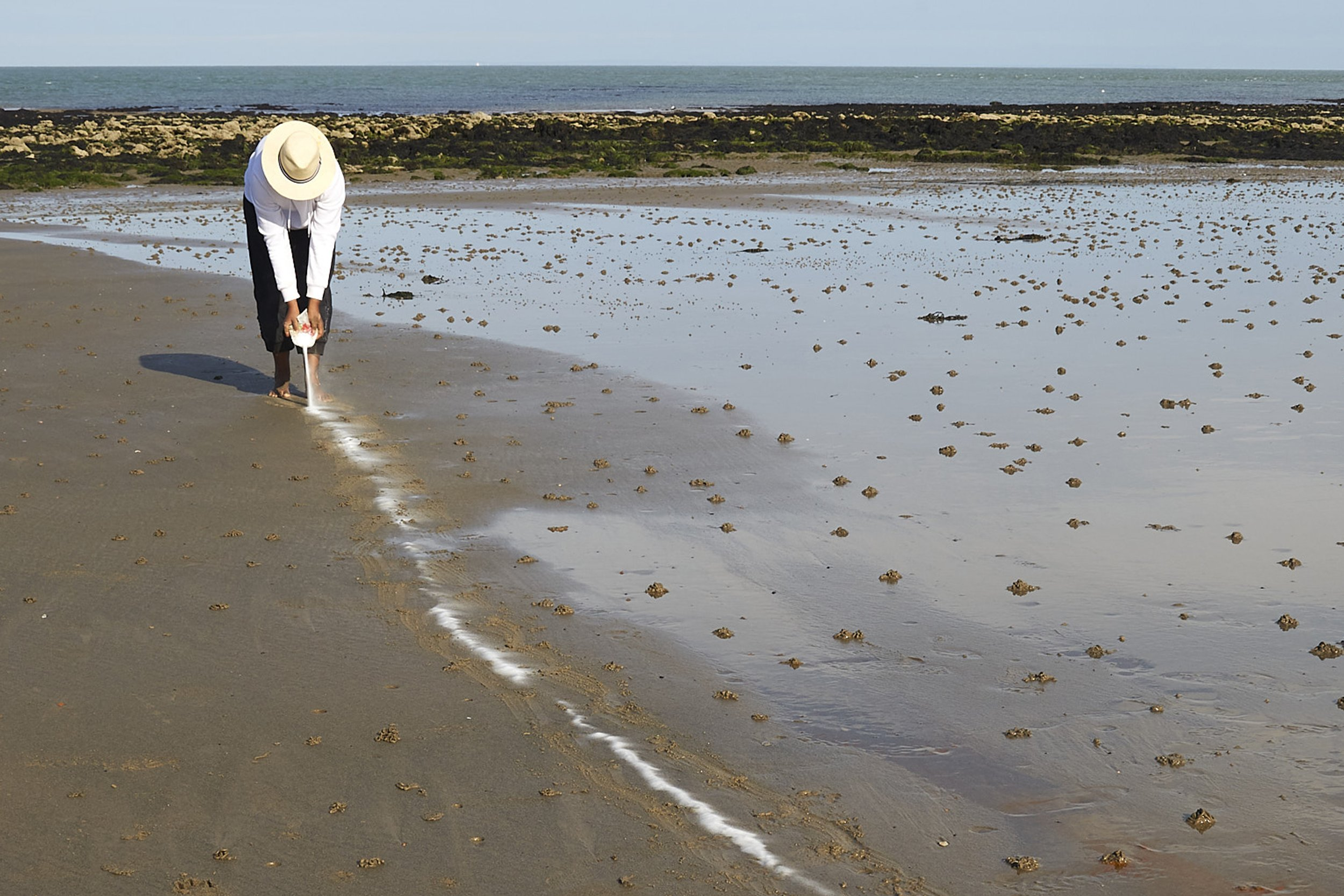 The artist walks backwards along the shoreline, pouring out a trail of white powder