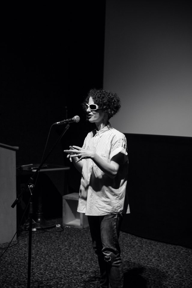 A black and white photo of Aislinn Thomas standing, speaking at a microphone. She is wearing a striped collared shirt rolled up at the sleeves, and is gesturing with her hands. She is wearing jeans and white sunglasses. Her skin is pale and her hair is cut in a short curly bob.