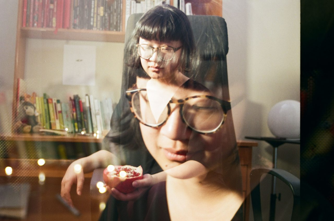 An image of Jane Shi with black bangs and chin-length hair. She is wearing a v-neck black shirt and has large, brown tortoise-shell glasses.  She is holding half a pomegranate in one open hand, and behind her is a desk with a shelf of books and a stuffed toy monkey. There is a close up of her face superimposed on the photograph, and the photograph is warm with sunlight.