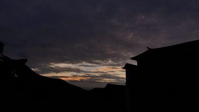 photo of sunrise over dark chinese roofs