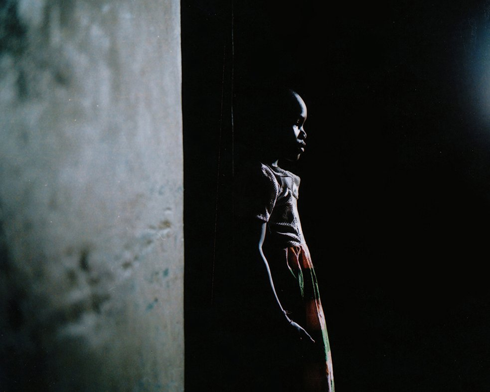 young girl stands only half-visibly against a wall in the shadows